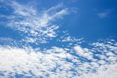 Fluffy white clouds on a blue sky. Clear sunny day. Background. Stock Images