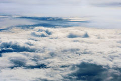 Fluffy white clouds and blue sky seen from airplane. Royalty Free Stock Photography