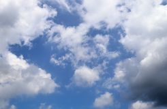 Fluffy white clouds on a clear blue sky stock photo