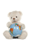 Fluffy white teddy bear with a globe Royalty Free Stock Photography