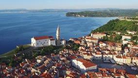 Flug über alter Stadt Piran in Slowenien, Luftpanoramablick mit alten Häusern, St- George` s Gemeinde-Kirche und Tartini quadrier stock video