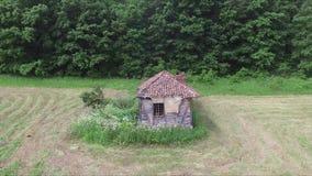 Flug über dem alten verlassenen Haus mitten in der Wiese stock video