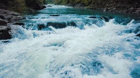 Flug über dem hetzenden Gebirgsfluss und dem Wasserfall, blau mitten in dem Wald und den Bergen Langer Berührungsschuß E stock footage