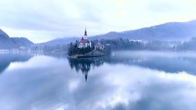 Flug über dem See geblutet mit Blick auf die Kapelle stock footage
