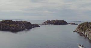 Flug über Fjord mit dem Fischerboot, das Bank mit Haus führt stock video
