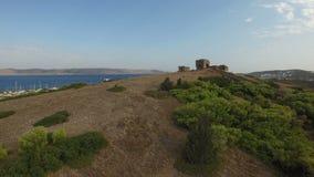 Flug über Hügel mit grünen Büschen und Ruinen einer historischen Festung auf die Oberseite stock video footage