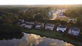 Flug über Nachbarschaft durch See bei Sonnenuntergang stock footage