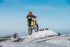 Flug des Motorradrennläufers auf einem Hintergrund des blauen Himmels nach Sprung Lizenzfreie Stockfotos