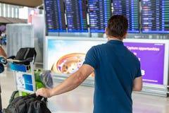 Flug-Informationsbildschirm des Mannes aufpassender, zum auf seinem f zu überprüfen lizenzfreie stockfotos
