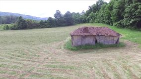 Flug nahe bei altem verlassenem Häuschen nahe bei dem Wald in der Wiese stock video