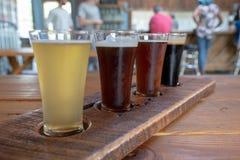 Flug von vier Bieren auf Behälter mit Leuten im Hintergrund stockbild