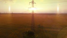 Fluga för kamera för ljus för afton för FLYG- Hög-spänning tornsommar varm upp near metallstrukturkontur mitt emot solen arkivfilmer