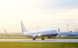 Fluga för passagerarenivå upp över tagande-avlandningsbana från flygplats på solnedgången Royaltyfria Foton