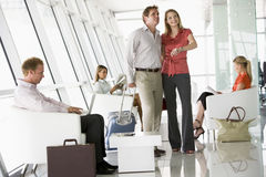 Fluggäste, die in Flughafenabflugaufenthaltsraum warten Lizenzfreie Stockfotografie
