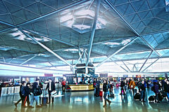 FLUGHAFEN LONDONS STANSTED, GROSSBRITANNIEN - 23. MÄRZ 2014: Passagiere in der Flughafenabfahrtarie, wartend durch die Auskunft u Stockfoto