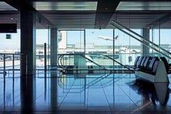 Flughafenabfahrtaufenthaltsraumsitzplätze und -rolltreppen Stockbild