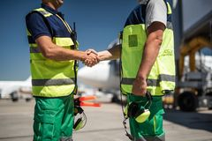 Flughafenarbeitskräfte, die Hände rütteln stockbild