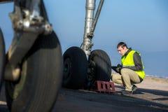 Flughafenarbeitskraft, die Fahrgestelle überprüft Stockbild