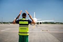 Flughafenarbeitskraft, die Passagierflugzeug und das Signalisieren betrachtet stockfoto