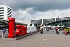 Flughafenquadrat mit Amsterdam-Logo und unbekanntem tra Lizenzfreie Stockfotografie