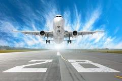 Flughafenrollbahn Nr. 28 und Flugzeug entfernen sich in zum Horizont und zu den malerischen Federwolkewolken im blauen Himmel Stockbild