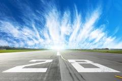 Flughafenrollbahn in zum Horizont und zu den malerischen Federwolkewolken im blauen Himmel Lizenzfreies Stockfoto