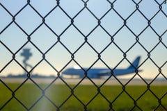Flughafensicherheitszaun mit Flugzeugen Stockfotografie
