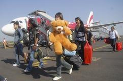 Fluglinienpassagiere, die weg von einem Flugzeug im Solo besteigen Lizenzfreies Stockbild