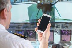 Fluglinienpilot, der intelligentes Telefon verwendet Stockbild