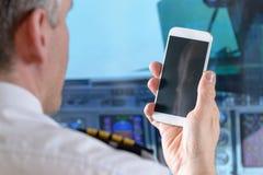 Fluglinienpilot, der intelligentes Telefon verwendet Stockfotos