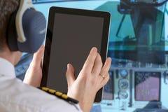 Fluglinienpilot, der Tablette verwendet Stockfoto