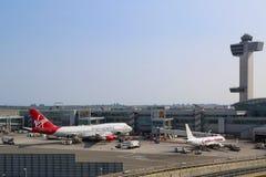 Flugsicherungs-Turm und Anschluss 4 mit Virgin Atlantic Boeing 747 und Caribbean Airlines Boeing 737 an den Toren in JFK Stockfotos