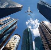 Flugzeug über Bürogebäuden Stockfotos
