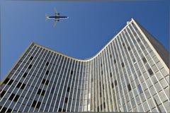 Flugzeug über einem modernen Glasgebäude Stockbild
