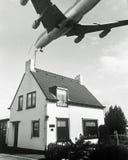 Flugzeug über Haus lizenzfreie stockfotografie
