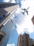 Flugzeug über Bürogebäuden. Stockbild
