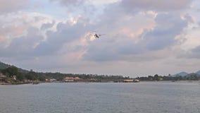 Flugzeug, das über tropischen Berg fliegt, den das Flugzeug auf der Insel gegen bewölkten Sonnenunterganghimmel landet Langsame B stock footage