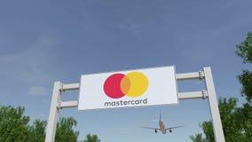 Flugzeug, das über Werbungsanschlagtafel mit MasterCard-Logo fliegt Redaktionelle Wiedergabe 3D Lizenzfreies Stockbild