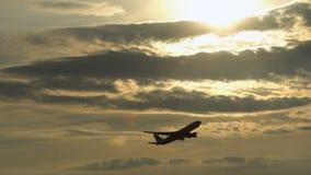 Flugzeug, das bei dem Sonnenuntergang sich entfernt stock video footage