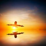 Flugzeug, das bei Sonnenuntergang sich entfernt lizenzfreies stockbild