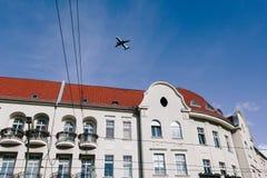 Flugzeug, das niedrig über Gebäude, Anflug fliegt lizenzfreie stockbilder