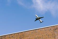 Flugzeug, das niedrig über Gebäude, Anflug fliegt lizenzfreies stockfoto