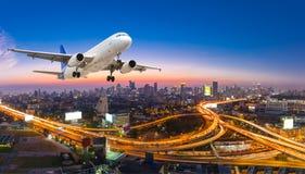 Flugzeug entfernen sich über der Szene der Panoramastadt in der Dämmerung stockfotografie