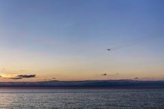 Flugzeug fliegt über das Meer Stockbild