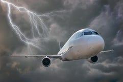 Flugzeug fliegt in Sturm Dunkle Wolken und Blitz im Hintergrund Lizenzfreies Stockfoto