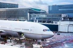 Flugzeug am Flughafenabfertigungsgebäude Stockbilder