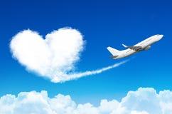 Flugzeug im blauen Himmel mit den Wolken, eine Spur in Form einer Wolke des Herzens hinterlassen Lizenzfreies Stockbild