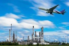 Flugzeug im Himmel über Erdölraffineriefabrikindustrie Stockbild