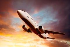 Flugzeug im Himmel bei Sonnenuntergang Lizenzfreies Stockbild