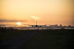 Flugzeug landet während des Sonnenaufgangs Lizenzfreie Stockfotografie